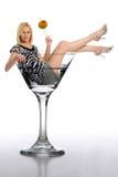 Mujer rubia joven en un vidrio de martini Imágenes de archivo libres de regalías