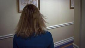Mujer rubia joven en vestido azul que camina en el pasillo del vestíbulo en el hotel de la huésped almacen de video