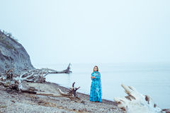 Mujer rubia joven en vestido en el banco del golfo por la tarde imágenes de archivo libres de regalías