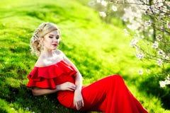 Mujer rubia joven feliz en retrato de la forma de vida del jardín de flores de la primavera imagen de archivo