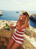 Mujer rubia joven feliz en sombrero con la bebida que presenta en el mediterrane imagen de archivo
