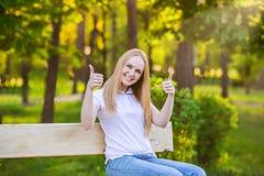 Mujer rubia joven feliz que da los pulgares para arriba en un fondo verde del sol Imagenes de archivo