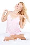 Mujer rubia joven feliz que estira en cama Imágenes de archivo libres de regalías