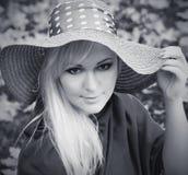Mujer rubia joven hermosa con el pelo largo en sombrero negro y wh Fotografía de archivo