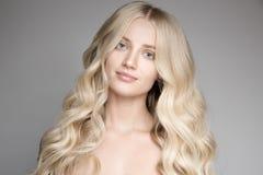 Mujer rubia joven hermosa con el pelo ondulado largo Fotos de archivo libres de regalías