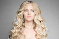 Mujer rubia joven hermosa con el pelo ondulado largo Imagen de archivo