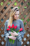 Mujer rubia joven hermosa con el ramo de los tulipanes encendido contra la perspectiva de una cerca de madera Imagenes de archivo