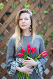 Mujer rubia joven hermosa con el ramo de los tulipanes encendido contra la perspectiva de una cerca de madera Fotografía de archivo libre de regalías