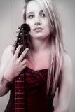 Mujer rubia joven hermosa con la camiseta de la guitarra eléctrica y de la mirada Imagen de archivo