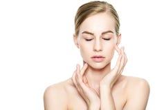 Mujer rubia joven hermosa con la piel perfecta que toca su cara Tratamiento facial Cosmetología, belleza y concepto del balneario foto de archivo