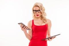 Mujer rubia joven hermosa con los vidrios en la tenencia roja de la camiseta Fotografía de archivo libre de regalías