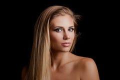 Mujer rubia joven hermosa de los ojos verdes con salud larga del straith imagenes de archivo
