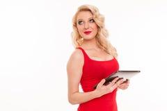 Mujer rubia joven hermosa en la camiseta roja que sostiene comp de la tableta Imagen de archivo libre de regalías
