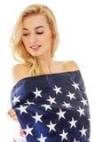 Mujer rubia joven hermosa envuelta en bandera americana Imagen de archivo libre de regalías