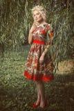 Mujer rubia joven hermosa que camina en el parque Foto de archivo libre de regalías