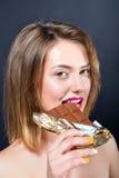 Mujer rubia joven hermosa que come la barra de chocolate Fotos de archivo