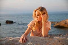 Mujer rubia joven hermosa que descansa sobre una playa en la oscuridad adentro temprano Imágenes de archivo libres de regalías