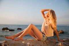 Mujer rubia joven hermosa que descansa sobre una playa en la oscuridad adentro temprano Imagen de archivo