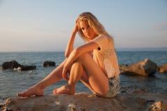 Mujer rubia joven hermosa que descansa sobre una playa en la oscuridad adentro temprano Foto de archivo