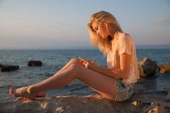 Mujer rubia joven hermosa que descansa sobre una playa en la oscuridad adentro temprano Foto de archivo libre de regalías