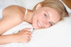 Mujer rubia joven hermosa que despierta y que sonríe en una cama blanca imagen de archivo