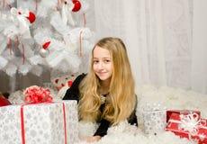 Mujer rubia joven hermosa que miente en el Año Nuevo con los presentes cerca del árbol de navidad, tiro del estudio Foto de archivo