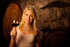 Mujer rubia joven hermosa que prueba el vino rojo en una bodega Fotos de archivo