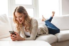 Mujer rubia joven hermosa que se relaja en un sofá imagenes de archivo
