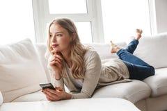 Mujer rubia joven hermosa que se relaja en un sofá imagen de archivo