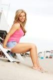 Mujer rubia joven hermosa que se sienta descalzo en la playa Fotografía de archivo