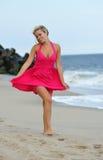 Mujer rubia joven imponente que recorre en la playa Imagenes de archivo