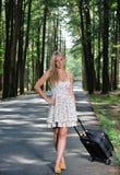 Mujer rubia joven imponente w/suitcase por el camino Imagenes de archivo