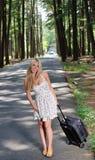 Mujer rubia joven imponente w/suitcase por el camino Imagen de archivo libre de regalías