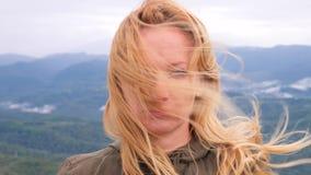 Mujer rubia joven infeliz que se coloca encima de una montaña en un fondo de nubes ella mira tristemente la cámara almacen de metraje de vídeo