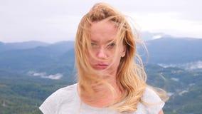 Mujer rubia joven infeliz que se coloca encima de una montaña en un fondo de nubes ella mira tristemente la cámara E almacen de metraje de vídeo
