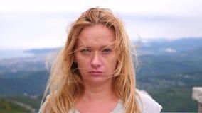 Mujer rubia joven infeliz que se coloca encima de una montaña en un fondo de nubes ella mira tristemente la cámara E metrajes