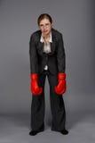 Mujer rubia joven irresoluta cansada en traje de negocios gris oscuro, Imágenes de archivo libres de regalías
