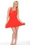 Mujer rubia joven juguetona atractiva atractiva que lleva a Mini Dress rojo corto Imágenes de archivo libres de regalías