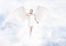 Mujer rubia joven magnífica como ángel en cielo Foto de archivo