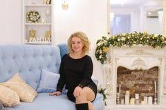 Mujer rubia joven maravillosa que sonríe y que plantea sentarse en el sofá Imágenes de archivo libres de regalías
