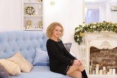 Mujer rubia joven maravillosa que sonríe y que plantea sentarse en el sofá Fotografía de archivo libre de regalías