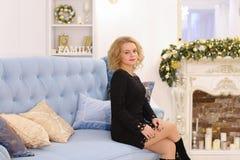 Mujer rubia joven maravillosa que sonríe y que plantea sentarse en el sofá Imagen de archivo