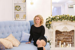 Mujer rubia joven maravillosa que sonríe y que plantea sentarse en el sofá Fotos de archivo libres de regalías