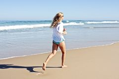 Mujer rubia joven que activa en la playa Imágenes de archivo libres de regalías