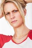 Mujer rubia joven que arruga su frente cuidadosamente Imagen de archivo libre de regalías