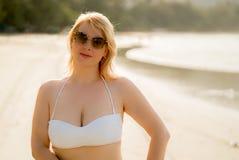 Mujer rubia joven que camina en bikini en la playa Imagenes de archivo
