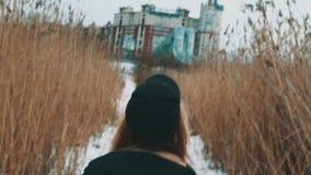 Mujer rubia joven que camina en la trayectoria de la nieve entre el bastón teñido en día nublado del invierno almacen de video
