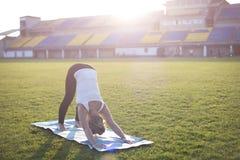 Mujer rubia joven que ejercita yoga en parque Foto de archivo libre de regalías