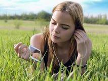 Mujer rubia joven que escucha la música con los auriculares al aire libre Imagenes de archivo