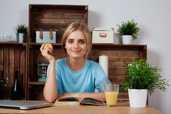 Mujer rubia joven que estudia para el hogar de la universidad Foto de archivo